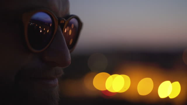 man wearing fashionable eyewear. lights reflecting in glasses - sunglasses stock videos & royalty-free footage