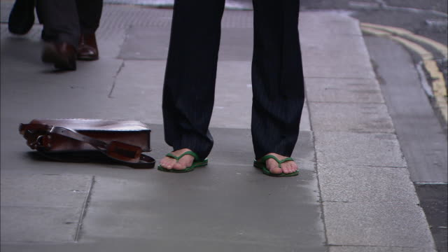 a man wearing flip-flops and a business suit, picks up a satchel off the sidewalk. - satchel stock videos & royalty-free footage