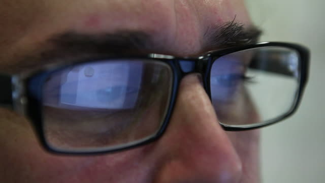 CU Man wearing glasses looking to video monitor / Sao Paulo, Brazil