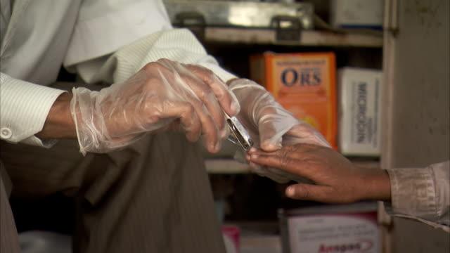 vidéos et rushes de a man wearing glove clips a boy's fingernails. - doigt humain