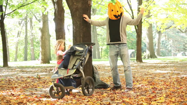 ms pan man wearing halloween pumpkin mask and little girl pushing an empty stroller  / toronto, ontario, canada - kelly mason videos stock videos & royalty-free footage
