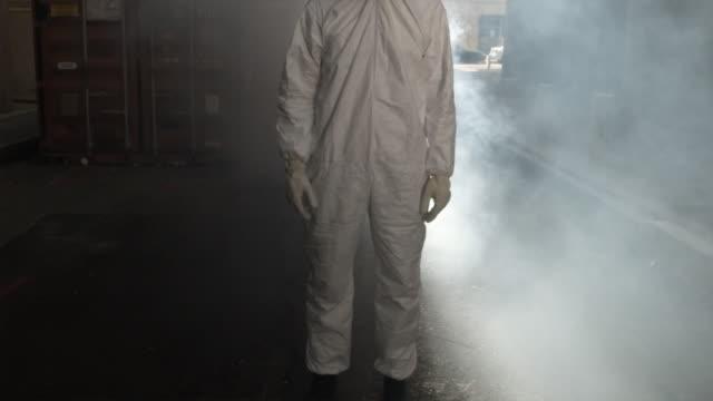 SLO MO MS TU Man wearing HAZMAT suit and gas mask in smoke, Atlanta, Georgia, USA