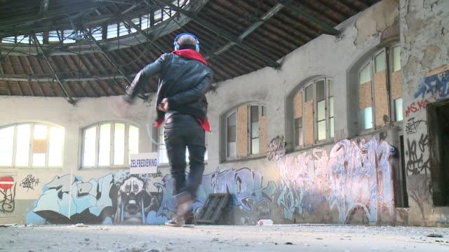 MS man wearing head phones dancing in warehouse, Gent, Belgium
