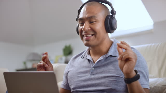vídeos de stock e filmes b-roll de man wearing headphones and dancing while listening to music sitting in his living room - 40 44 anos