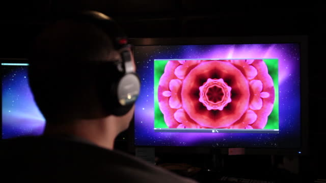 CU Man wearing headphones moving head to music as watching on computer screen with graphics / Los Angeles, California, United States