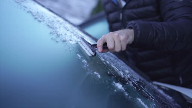 vidéos et rushes de man wearing health mask scraping ice off windshield on mountain pass - froid