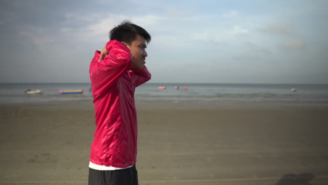 vidéos et rushes de homme utilisant le capot et courant sur la plage - veste et blouson