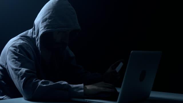 Man dragen Hooded Shirt en met behulp van Laptop In donker voor kappen