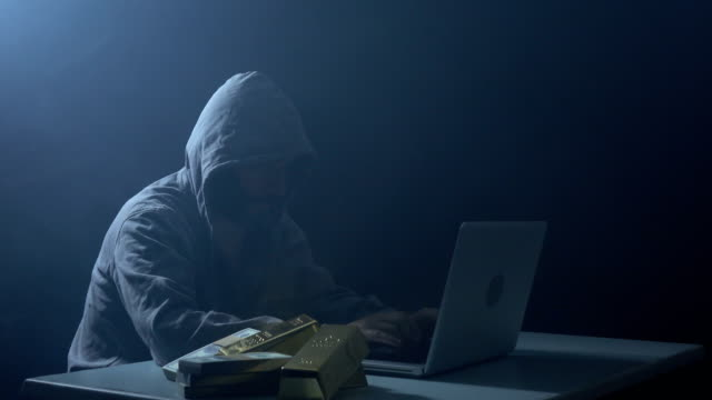 Man Wearing Hooded Shirt And Using Laptop In Dark To Hack