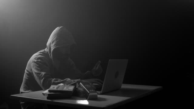 man wearing hooded shirt and using laptop in dark to hack - hooded top stock videos & royalty-free footage
