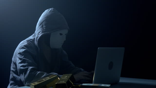 man wearing hooded shirt and using laptop in dark to hack - identity stock videos and b-roll footage