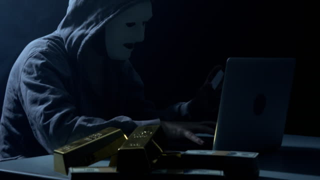 man wearing hooded shirt and using laptop in dark to hack - cracker stock videos and b-roll footage