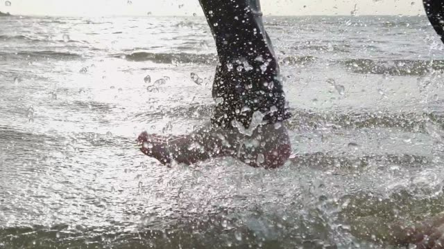 man wearing jeans is running in shallow water on a beach in the sun - tina terras michael walter stock videos & royalty-free footage