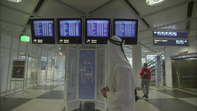 stockvideo's en b-roll-footage met ws zi cu man wearing kaffiyeh looking at airport arrival and departure board / munich, germany - münchen vliegveld
