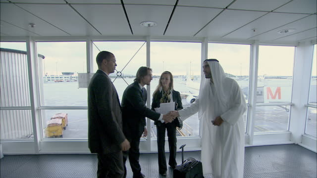 WS Man wearing kaffiyeh shaking hands and looking at documents with three other businesspeople in airport / Munich, Germany