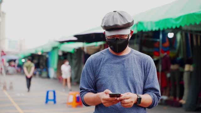 マスクを着用した男性は、割引看板で店の前で働くcovid-19を保護します, オンライン通信を使用している人々, 社会的な離散 - ビジカジ点の映像素材/bロール
