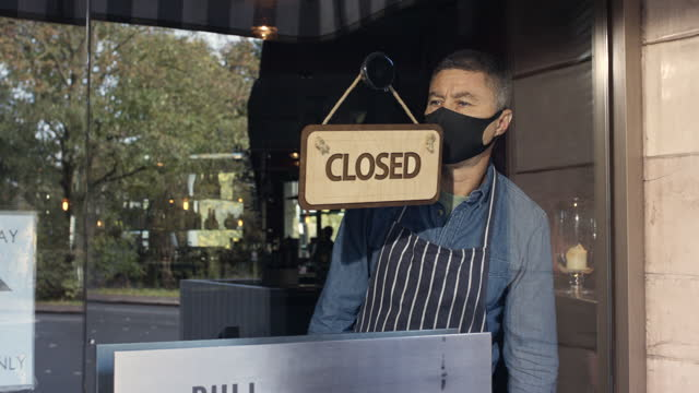 man wearing mask turning closed sign on restaurant window - non us film location stock videos & royalty-free footage
