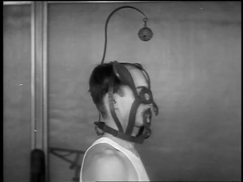 b/w 1932 ms profile man wearing metal mask with animal ears + bell on top turning + facing camera - torture stock videos & royalty-free footage