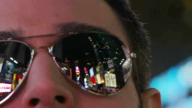 ECU FOCUSING PAN Man wearing mirror shades reflecting Times Square at night / New York City, New York, USA