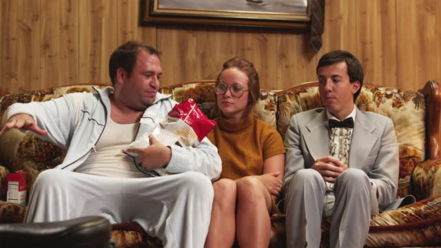ms man wearing pajamas, holding bag of chips sitting by nerdy couple on sofa / orem, utah, usa - uncomfortable stock videos and b-roll footage