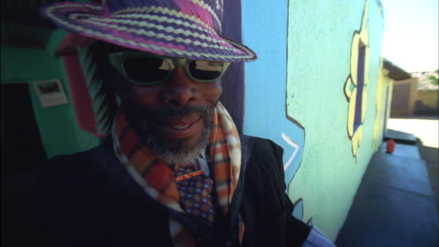man wearing patterned hat and scarf playing accordion in doorway of colourfully painted house available in hd. - piano key stock videos and b-roll footage