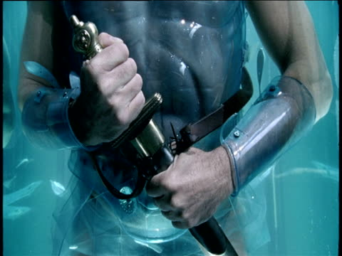 man wearing plastic centurion armour draws dagger while floating in water - dagger stock videos & royalty-free footage