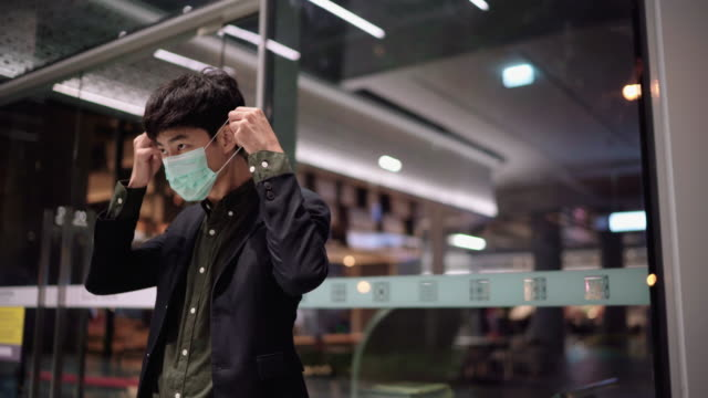 a man wearing pollution masks and walking down the street at night - pavement stock videos & royalty-free footage