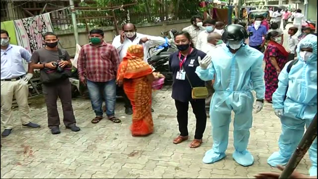 man wearing ppe and smart helmet to screen body temperature of people walking on road amidst covid19 crisis in mumbai's suburban area of dahisar on... - mid distance stock videos & royalty-free footage