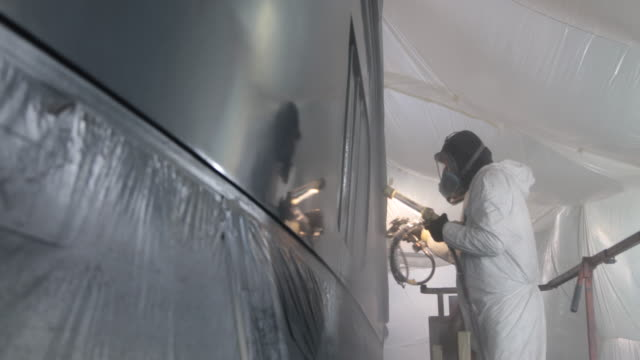 Man wearing protective clothing painting side of big boat in boatyard