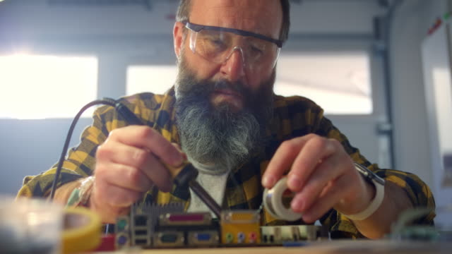 slo mo man wearing protective glasses while soldering a circuit board in his workshop - repairing stock videos & royalty-free footage
