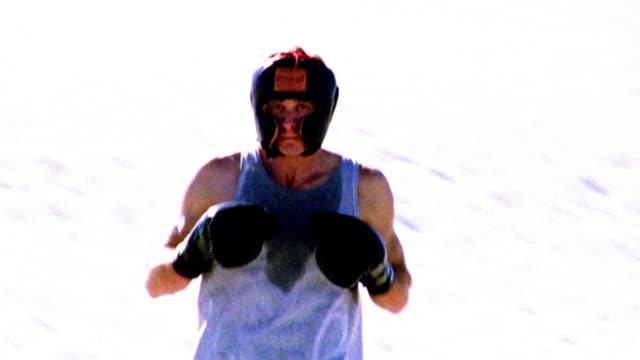 vídeos de stock e filmes b-roll de selective focus man wearing protective head gear jogging + boxing toward camera in desert / nm - super exposto