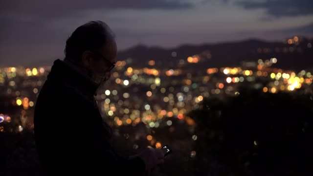 a man wearing protective mask looks at the mobile phone and enjoy the sunset at the carmel hill on may 17 2020 in barcelona spain some parts of spain... - wireless technology stock videos & royalty-free footage