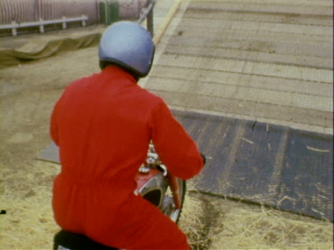 man wearing red jumpsuit and blue helmet riding small cycle motorcycle up wood ramp with steep incline that is also laden with international flags /... - jumpsuit stock videos and b-roll footage