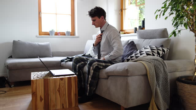 ws man wearing shirt, tie and pajamas while having a video conference on a laptop at home - pyjamas stock videos & royalty-free footage