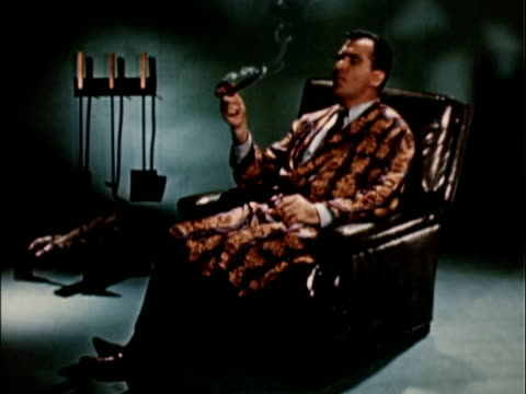 1956 ws man wearing smoking jacket on leather recliner / usa - sigaro video stock e b–roll