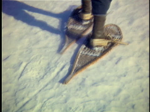 1965 cu man wearing snowshoes walks through snow, low section, vermont, usa - ウィンタースポーツ点の映像素材/bロール
