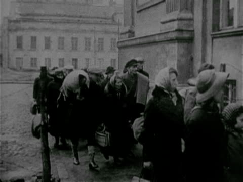 man wearing star on coat escorting jewish people, adults, children, families w/ suitcases, belongings in bundles, walking down sidewalk & into... - newsreel stock videos & royalty-free footage