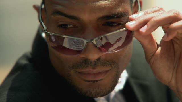 vídeos de stock, filmes e b-roll de ecu man wearing sunglasses looking around, jacksonville, florida, usa - espreitando