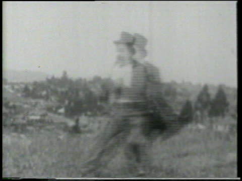 B/W 1915 man wearing top hat stopping on grassy field + dodging bullets fired from offscreen