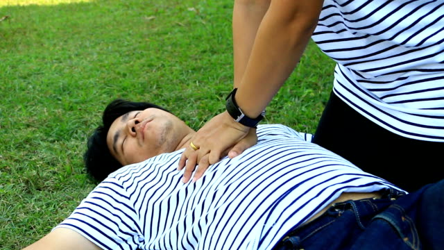 rescue cpr training to safe life man wearing t-shirt stripes lay down and women with white   long-sleeved shirt trains cpr on the grass background, concept in the process of   resuscitation (first aid - cpr stock videos & royalty-free footage