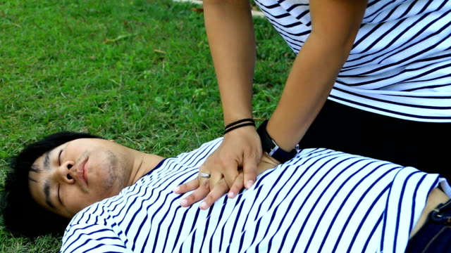 rescue cpr training to safe life man wearing t-shirt stripes lay down and women with white long-sleeved shirt trains cpr on the grass background, concept in the process of resuscitation (first aid) - cpr stock videos & royalty-free footage