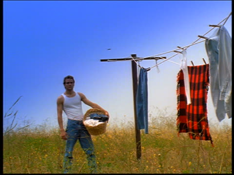 portrait man wearing undershirt + jeans holding basket next to clothesline in field - laundry basket stock videos and b-roll footage