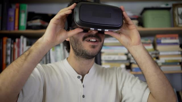 mann mit virtual-reality-kopfhörer in front der bibliothek zu hause - schutzbrille stock-videos und b-roll-filmmaterial