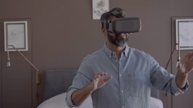 man wearing vr goggles in bedroom at home - virtuelle realität stock-videos und b-roll-filmmaterial