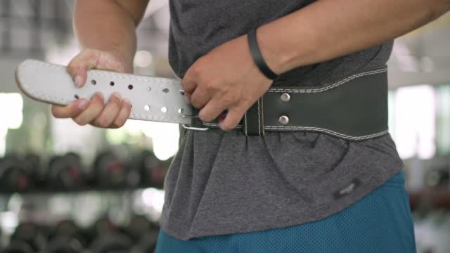 man bär tyngdlyftning bälte på gym - diskbänk bildbanksvideor och videomaterial från bakom kulisserna