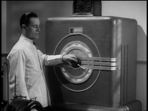 b/w 1937 ms man wearing white scientist coat turning knob on large machine - scientific experiment stock videos & royalty-free footage
