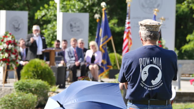 a man wears a powmia tshirt while listening during memorial day ceremonies at valhalla memory gardens may 29 2017 in bloomington ind a new war... - veterans of foreign wars of the united states stock videos & royalty-free footage