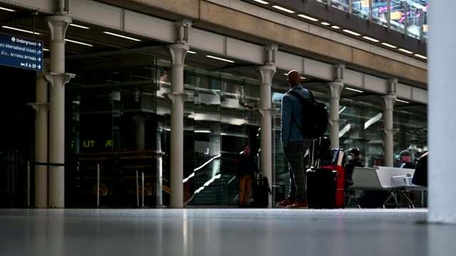man wears a protective mask as he waits for a train to begin boarding at st pancras international station on may 04, 2020 in london, england. from... - transportation stock videos & royalty-free footage
