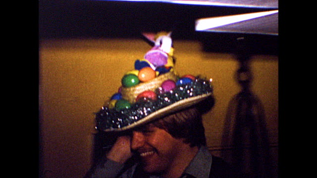 a man wears an easter straw hat with a bunny and eggs fastened on the crown and brim of the hat - bonnet stock videos & royalty-free footage