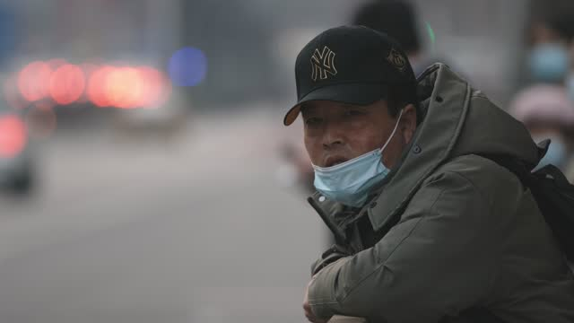 man wears protective face mask as he waits the bus on march 8, 2021 in beijing, china. china will steady increases in spending on automobiles and... - beijing stock videos & royalty-free footage